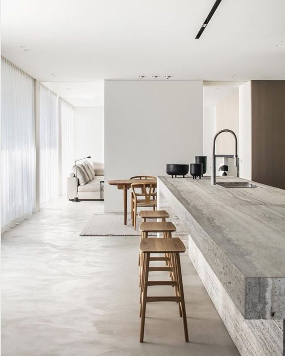 a minimalist kitchen with an oversized stone kitchen island and wooden stools plus all white walls around is chic
