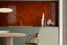 a minimalist kitchen with color – a hot red tile backsplash, sleek olive green cabinets, a curved table and chair plus a mosaic floor