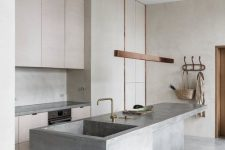 a minimalist kitchen with light stained cabinets, a concrete backsplash and a kitchen island with a sink, a chic pendant lamp