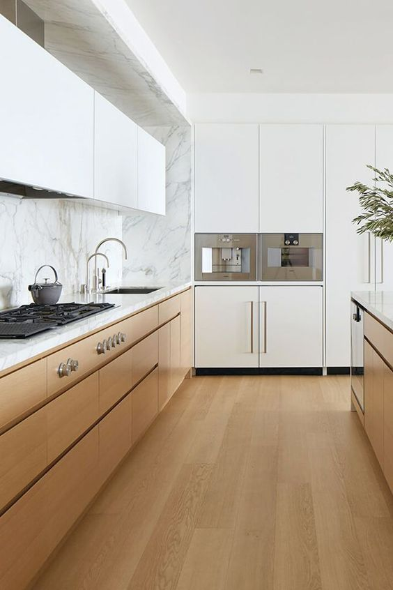 a minimalist kitchen with light-stained hardwood floors that match the lower cabinets, with sleek white cabinets and a marble backsplash