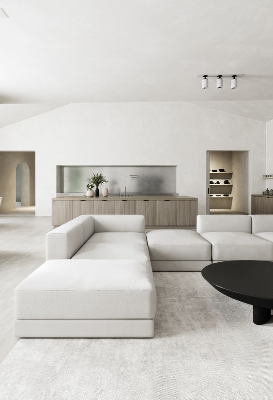 a minimalist living room with a kitchen here, with an oversized neutral sectional, a black coffee table and a stained cabinetry in the kitchen