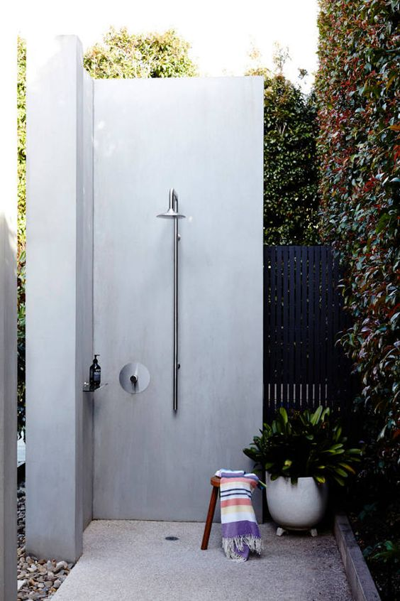 a minimalist outdoor shower space with a pebble floor, a potted plant and a colorful towel plus a living wall next to it