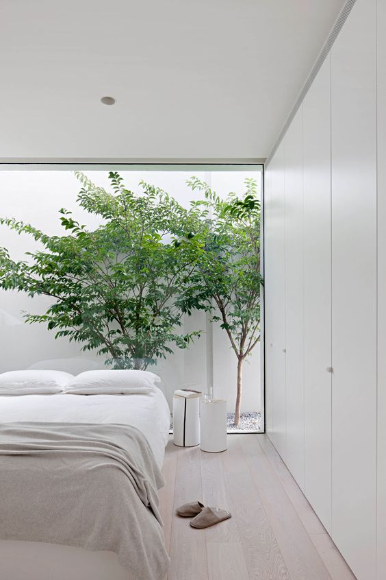 a minimalist white bedroom with a glazed wall with a view to the courtyard, sleek white storage units, simple furniture and side tables