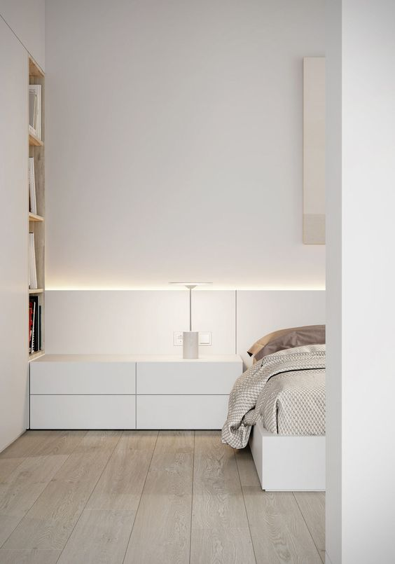 a minimalist white bedroom with sleek storage units and a bed, built-in lights and printed bedding is very cool