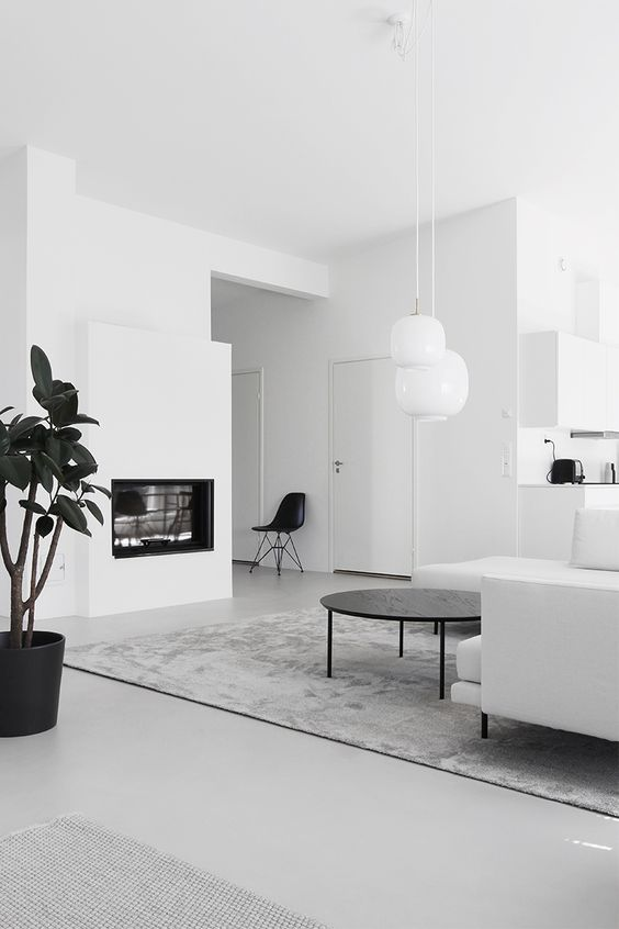 a minimalist white living room with a built-in fireplace, a white sofa and a black round coffee table, pendant lamps and black touches
