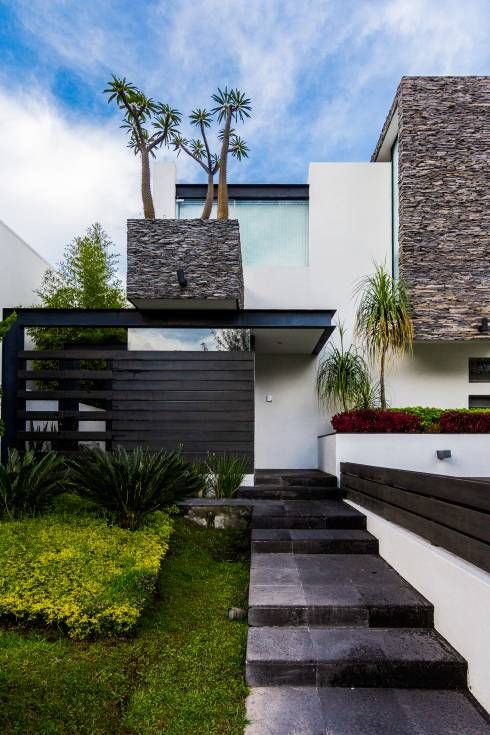 a modern and fresh front yard with stone tiles, with grasses, succulents and some trees inspires and welcomes in