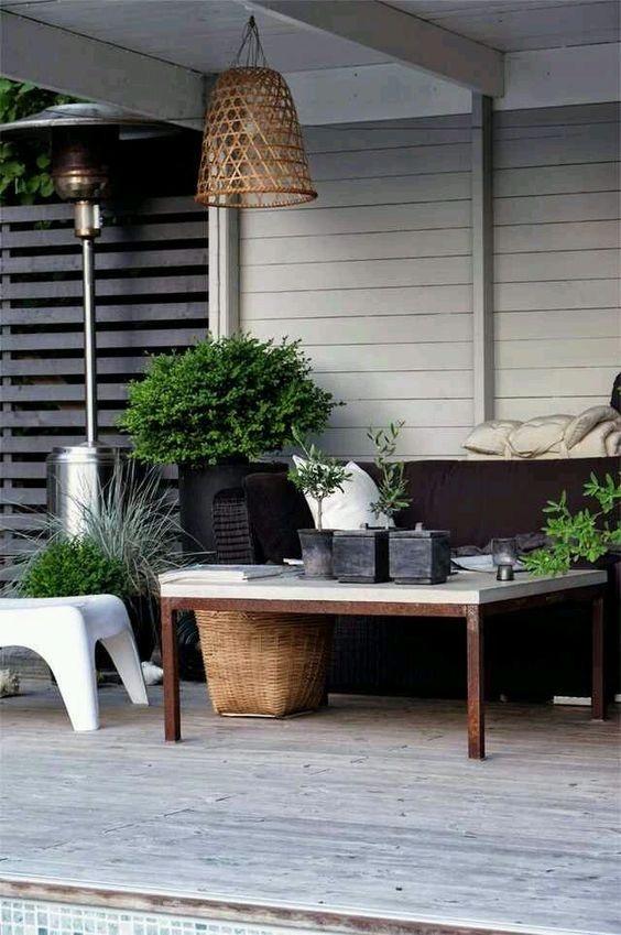a modern and lively summer terrace with a low table and chairs, a pendant woven lammp, potted greenery and a basket