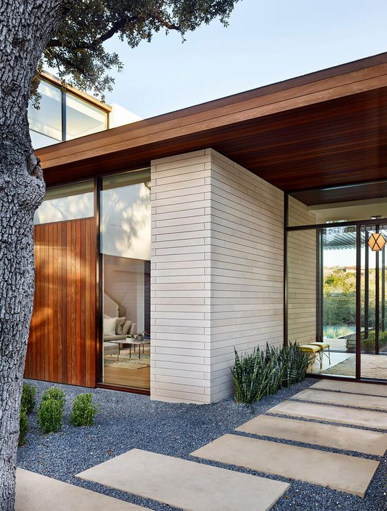 a modern and very laconic front yard with gravel, stone tiles, greenery, succulents plus a living tree is a very chic and stylish space