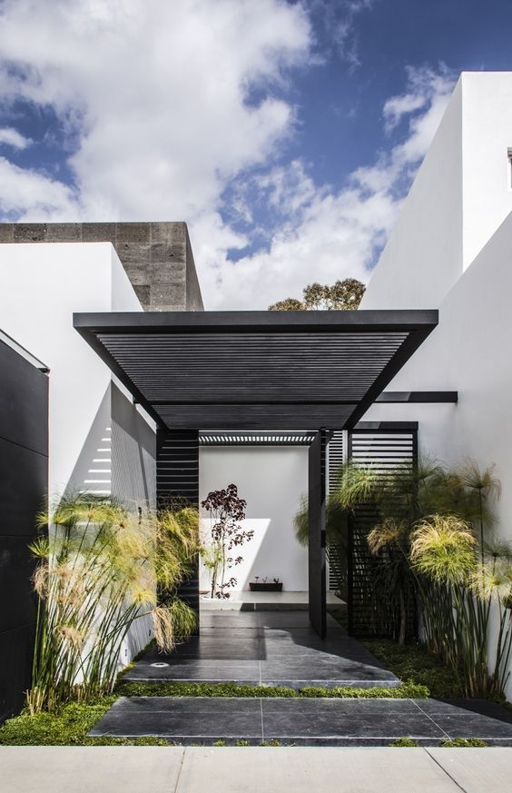 a modern front yard clad with dark tiles, with grass and tall plants and with a planked roof over the porch is very stylish and bold