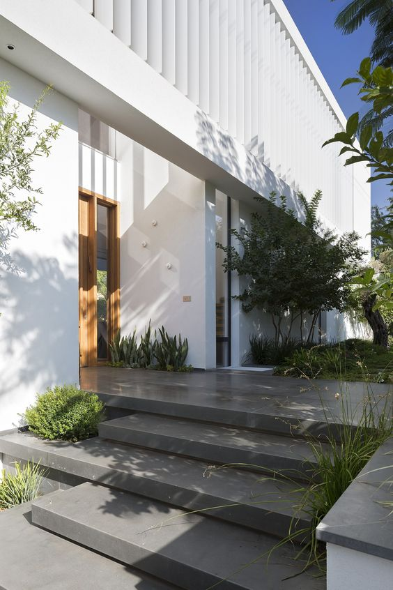 a modern front yard clad with stone tiles and with some greenery growing in the steps and with trees and succulents growing around the house