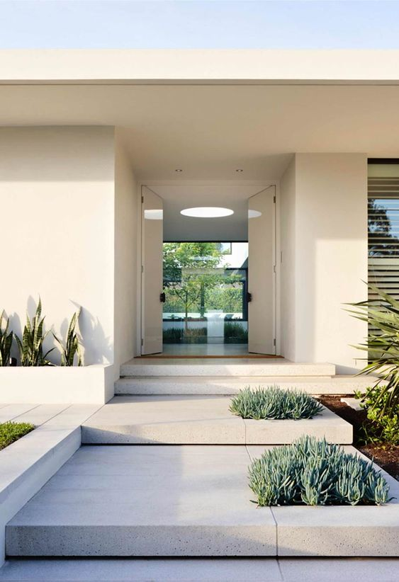 a modern front yard clad with stone tiles and with succulents and cacti growing right in the tables and in built-in planters is very sleek and elegant