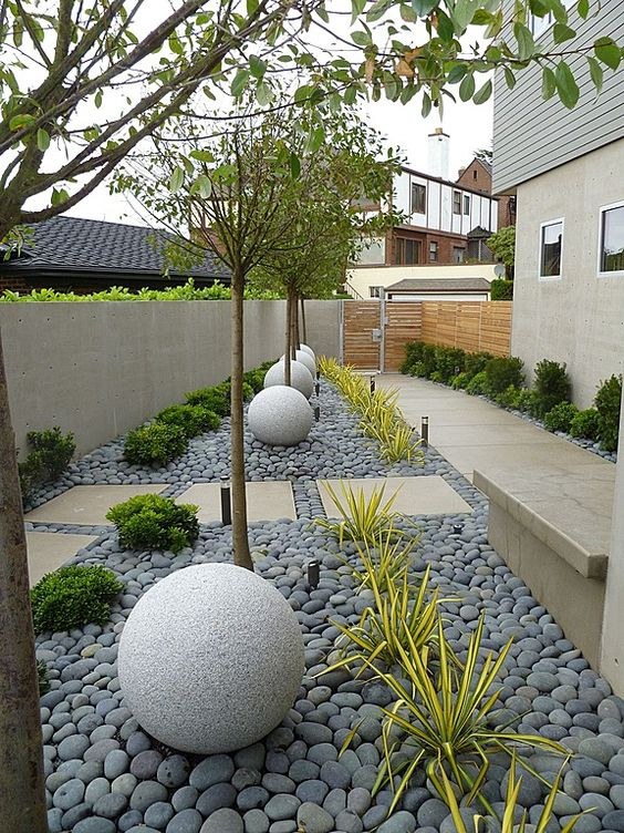 a modern front yard styled with tiles and grey pebbles, stone balls, trees, greenery and succulents is a stylish space that catches an eye