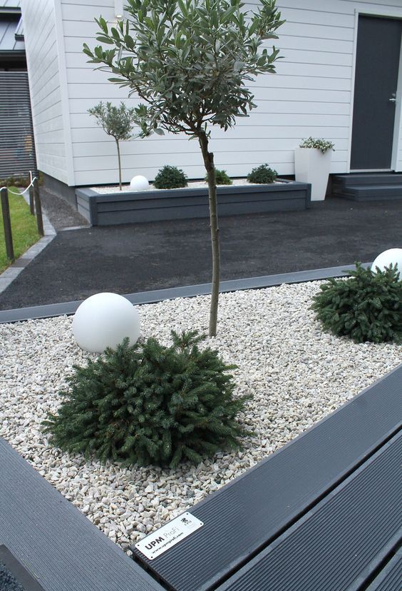 a modern front yard with a dark deck and neutral pebbles, greenery, trees and white balls plus elegant modern planters is a chic idea