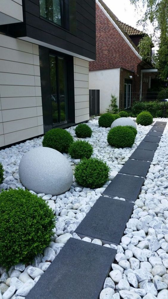 a modern front yard with large rocks and dark tiles for a contrast, greenery balls and oversized stone ones for bold landscaping