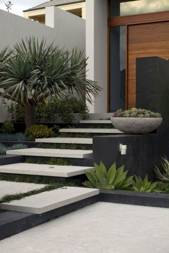 a modern front yard with neutral steps and greenery in between the steps, with trees and succulents around is a chc and bold space