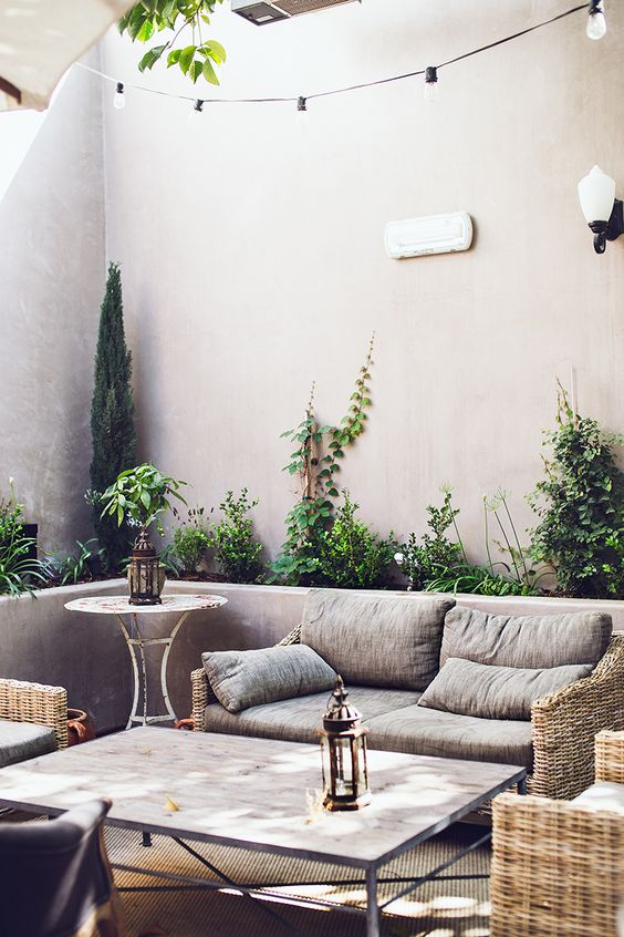 a modern neutral patio with elegant woven furniture, neutral textiles, a side table, los of potted plants and candle lanterns