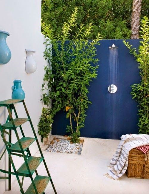 a modern outdoor shower space with a black wall, growing trees and plants, a ladder, a wicker ottoman with towels and base decor on the wall