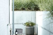 a modern outdoor shower with a wooden deck, a stool, potted plants, a shampoo and lots of grass growing around
