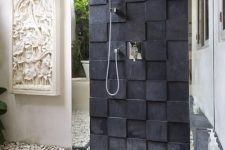 a modern outdoor shower with pebbles on the ground, with black tiles on the wall and ground, plus a roof over it
