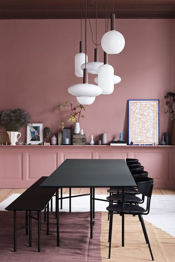 a modern pink dining room with pink paneled walls, a long shelf along the whole wall, a black dining set and a cluster of pendant lamps