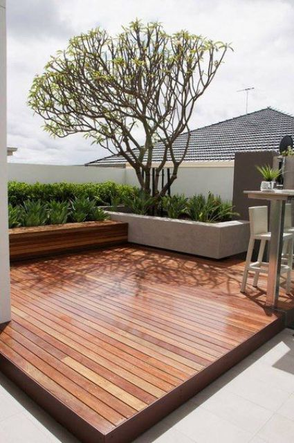 a modern rooftop terrace with a wooden deck, a dining space, potted greenery and a tree looks very laconic and very stylish