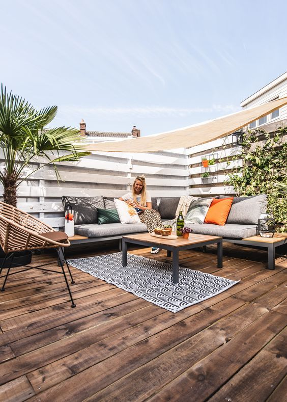 a modern summer deck with a built-in sectional, bold and printed pillows, potted plants and a round chair is a welcoming space to be