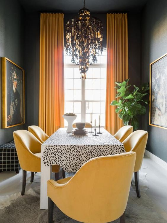 a moody dining room with black walls, a Dolmatin print table, yellow chairs, a unique and catchy chandelier and statement artworks