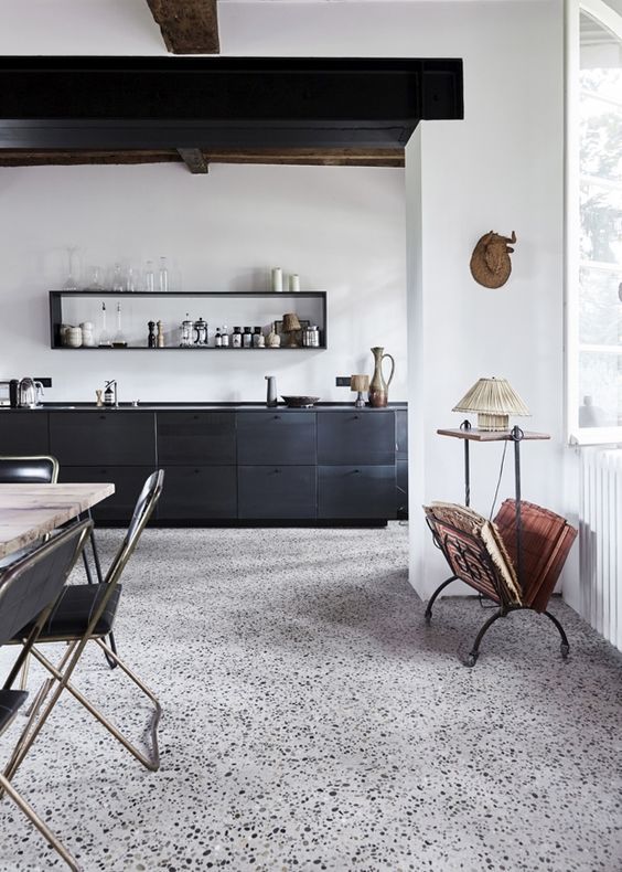 a moody kitchen and dining room with a black and white terrazzo floor, black cabients and chairs, black wooden beams on the ceiling