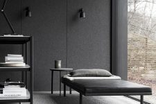 a moody minimalist living room with a glazed wall, a black daybed and side table, a fire pit and a shelving unit plus lamps