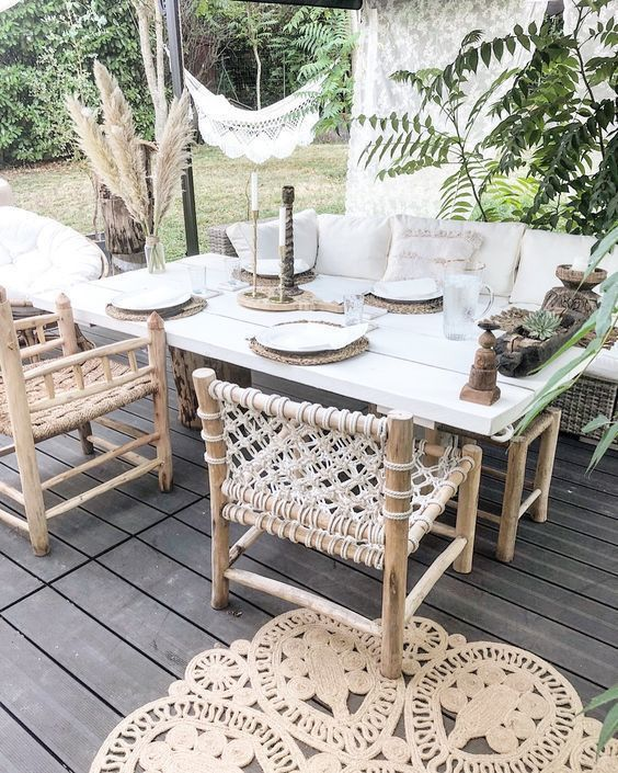a neutral boho dining space with a wicker sofa and woven chairs, a simple table, potted greenery and pampas grass and woven placemats