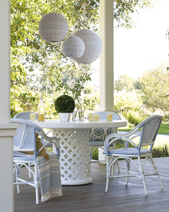 a neutral coastal dining space with a chic round table and white and blue rattan chairs plus white woven pendant lamps