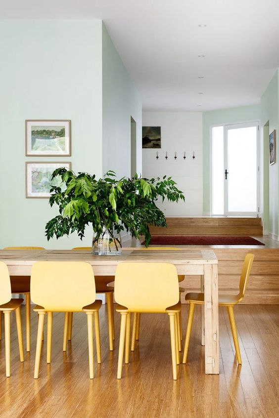 a peaceful dining room with light blue walls, a wooden dining table and yellow chairs, a small gallery wall is chic