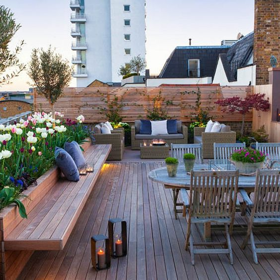 a peaceful rooftop terrace with a wooden deck, built-in furniture, a lovely wooden dining set, potted blooms and plants