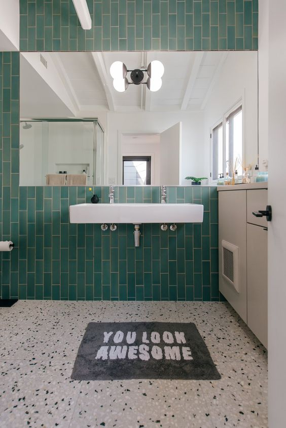 a pretty bright bathroom with turquoise skinny tiles and grey and white terrazzo flooring, white appliances and a large mirror