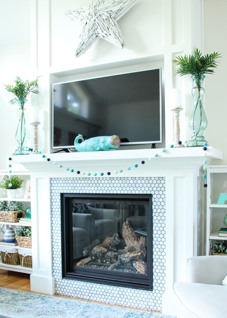 a pretty coastal mantel with a turquoise whale, green vases, a pompom garland in blues and a whitewashed driftwood star