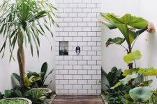 a pretty outdoor bathroom with a wooden deck and a subway tile wall, growing plants around is a very lovely space