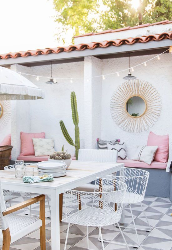 a pretty pastel summer terrace with a built-in grey bench and pink upholstery, a white table and white chairs, a potted cactus and a ligth string