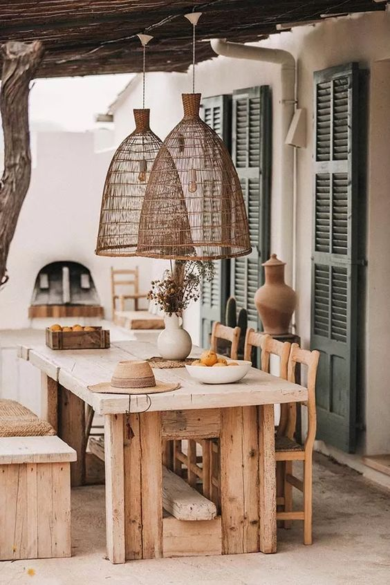 a pretty rustic outdoor dining space with a wooden table and a bench, with vintage chairs, pendant lamps and some greenery welcomes