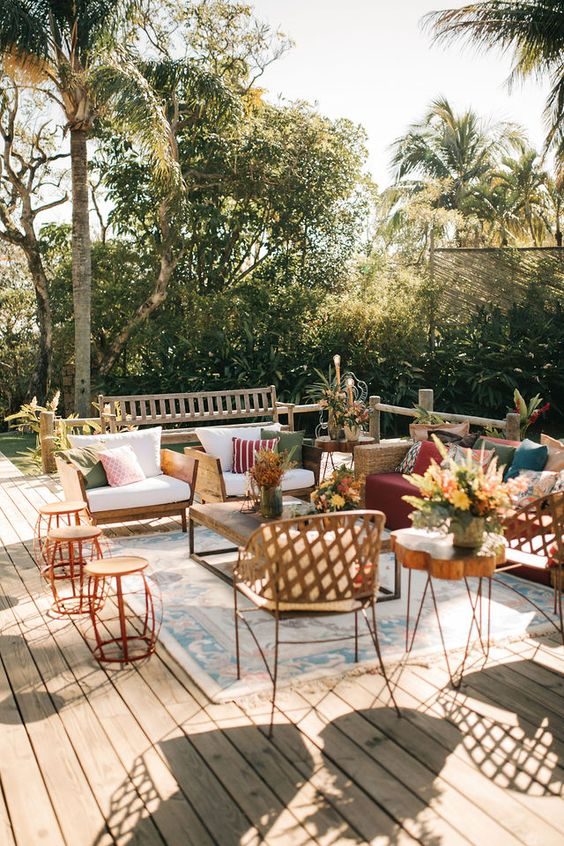 a pretty summer terrace with a wooden deck, modern wicker furniture, potted plants and blooms, a wood slice table and printed rugs