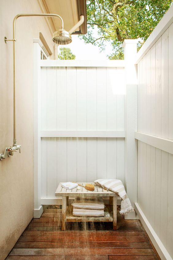 a private outdoor shower with wood planked walls and a bench with everything necessary is amazing and cool