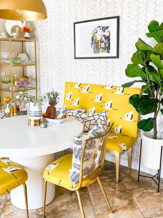 a quirky dining room with a gilded storage unit, a round table, whimsical yellow printed chairs and a loveseat plus a potted plant