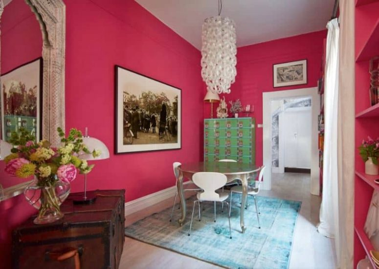 a quirky dining room with hot pink walls, a round metal table, a mirror in an ornated frame, blooms and a catchy chandelier