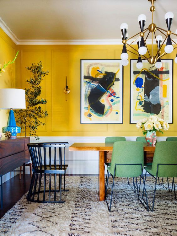 a quirky dining room with yellow walls, a bold gallery wall, a wooden table and green chairs, a retro chandelier and a potted plant