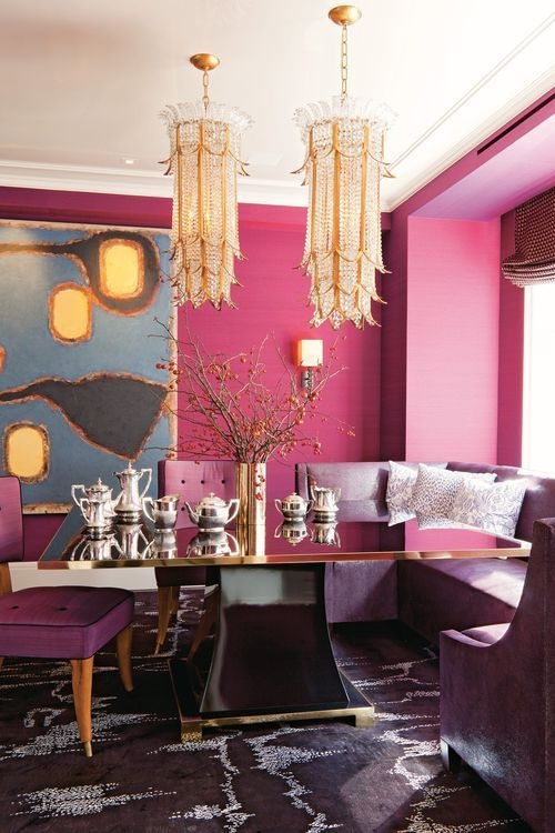 a quirky glam dining space with hot pink walls, a refined black and gold dining table, a built-in purple bench, two crystal chandeliers and an abstract artwork