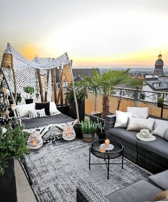 a refined boho rooftop terrace with chic sofas and a daybed, printed pillows, potted greenery and a palm tree and some lanterns