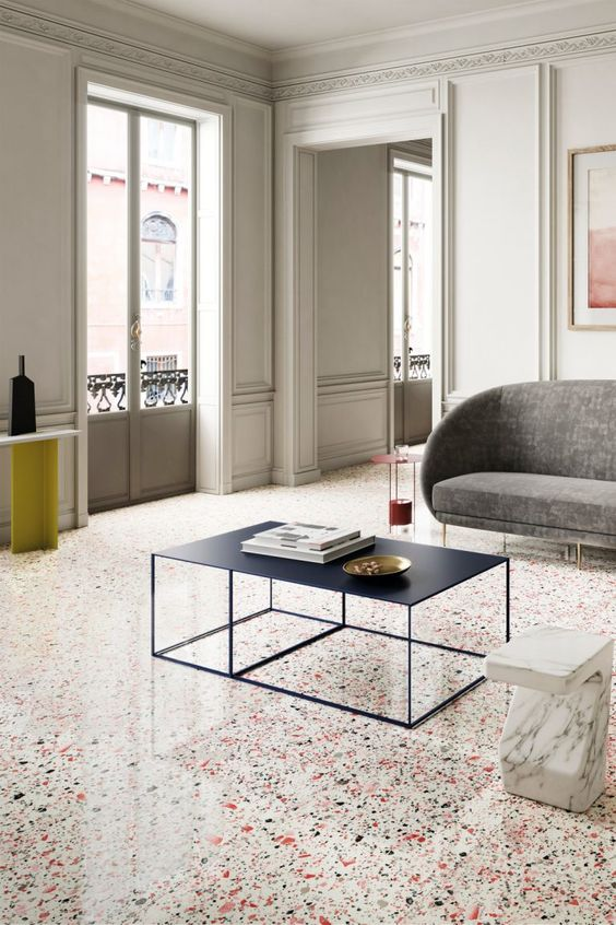 a refined contemporary living room with neutral panels on the walls, a bright terrazzo floor and chic and sophisticated furniture