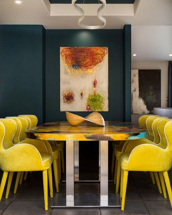 a refined formal dining space with a navy accent wall, lemon yellow chairs, a colorful table and a bold artwork on the wall