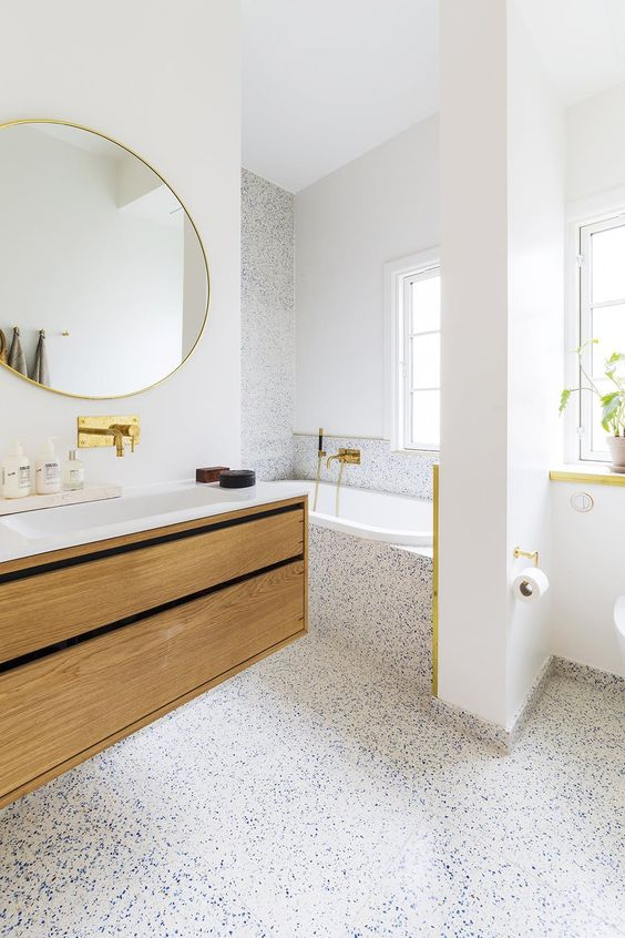 a refined light-filled bathroom with white walls and a white and blue terrazzo floor that covers one wall and the tub, too