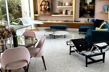 a refined living and dining room with a black and white terrazzo floor, a pink wall and a chic storage unit, statement artworks
