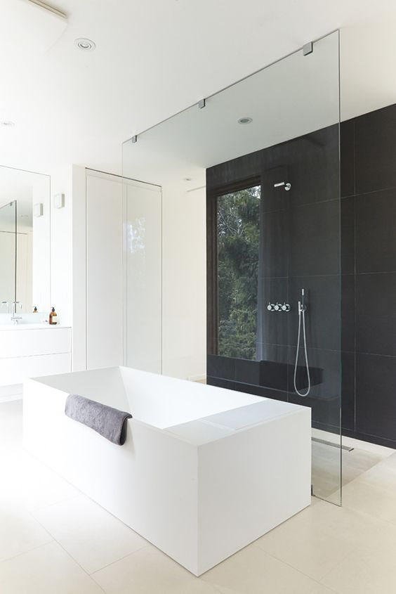 a refined minimalist bathroom with a black tile accent wall in the shower space, a white geometric tub and sleek white cabinets